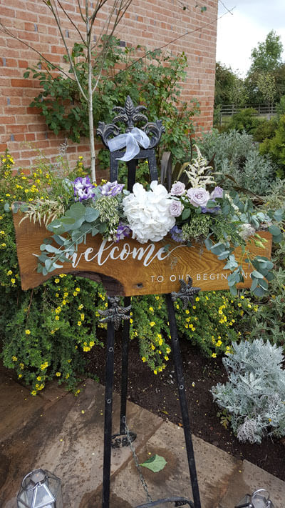 Weddings - Props For Hire - Wedding Sign 'Welcome to Our Beginning' Rustic Wood & Easel (Easel Stands Vary) - Flowers Extra