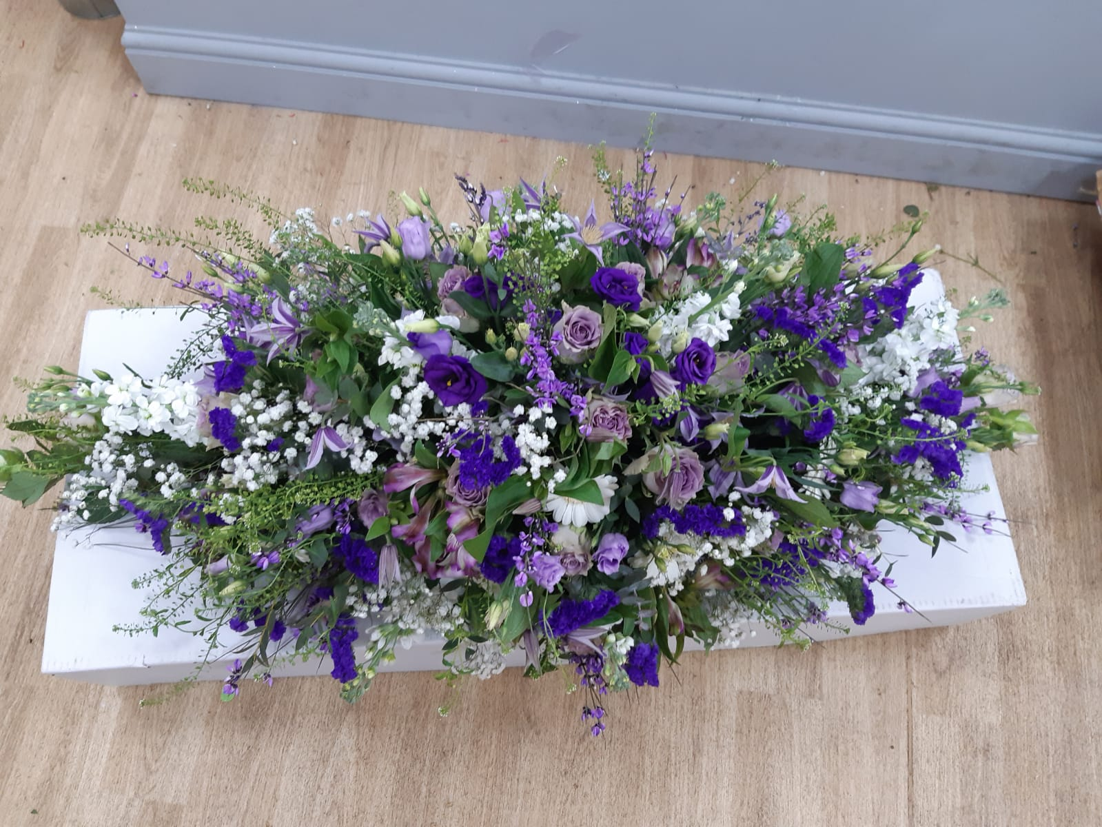 Funeral casket roses eustoma stock thlaspi clematis foliage statice broom germini