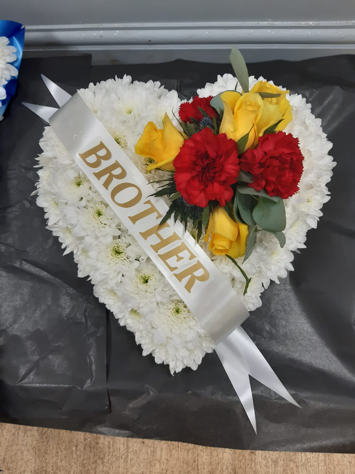 Funeral heart white base with roses carnations thistle